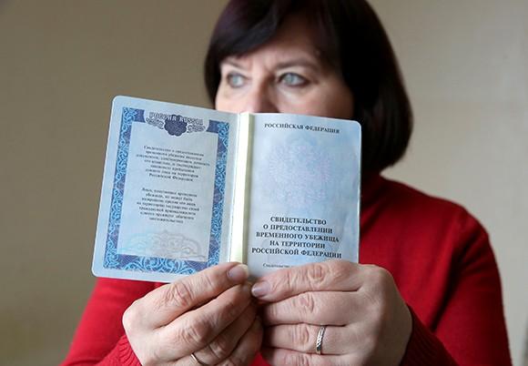 Женщина с документом, подтверждающем статус беженца